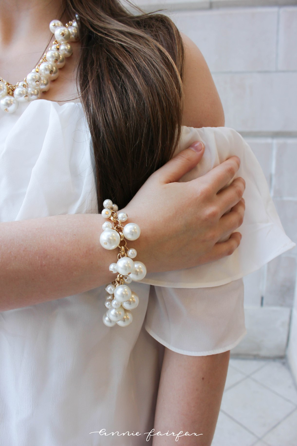 White off the shoulder dress with pearl necklace bracelet blush coach handbag purse date night formal spring summer look airy light